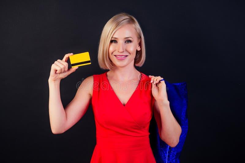 Attraktive blonde Frau in rotem Kleid hält eine Ledertasche in High Heels Full-Länge Studio in schwarzem Hintergrund gedreht stockbilder