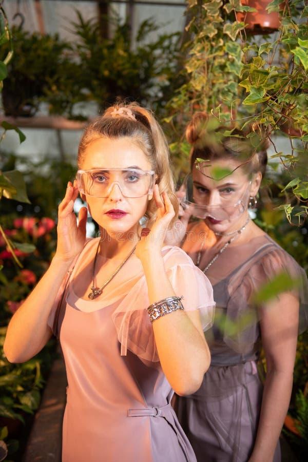 Attraktive blonde junge Frau, die transparente Gläser trägt stockfotos