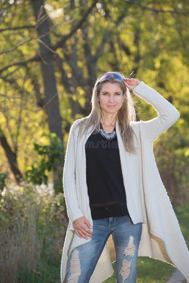 Attraktive blonde junge Frau mit unscharfem Hintergrund lizenzfreie stockfotos