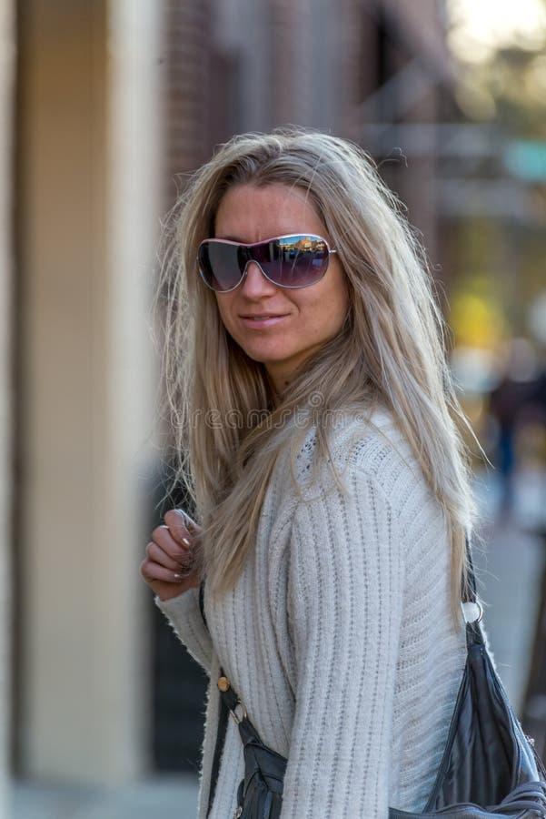 Attraktive blonde junge Frau mit unscharfem Hintergrund stockbilder