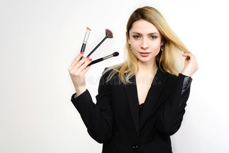 Attraktive blonde Make-upkünstler-Holdingbürsten lizenzfreie stockfotos