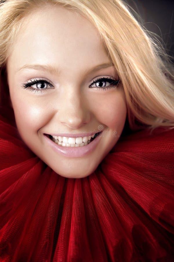 Attraktive blonde Schönheit im roten Theaterjabot lizenzfreie stockbilder