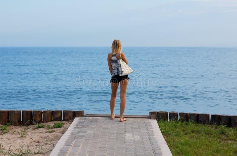 Attraktive blonde Stellung auf dem Strand stockfoto