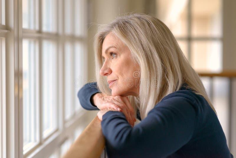 Attraktive blonde träumende Frauenstellung stockbild