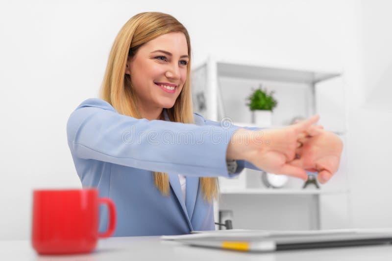 Attraktive Blondine an dem Arbeitsplatz dehnt das Sitzen am Schreibtisch im Büro aus lizenzfreie stockbilder
