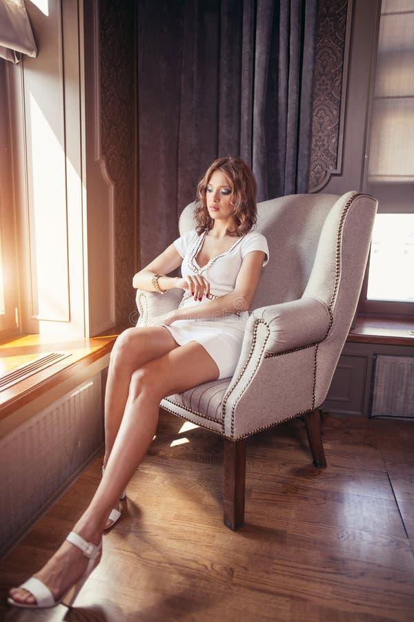 Attraktive Blondine, die auf Stuhl im Luxusinnenraum sitzen stockfoto