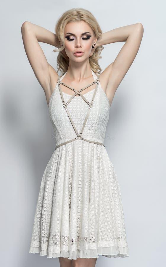 Attraktive Blondine im schönen weißen Kleid stockfotografie
