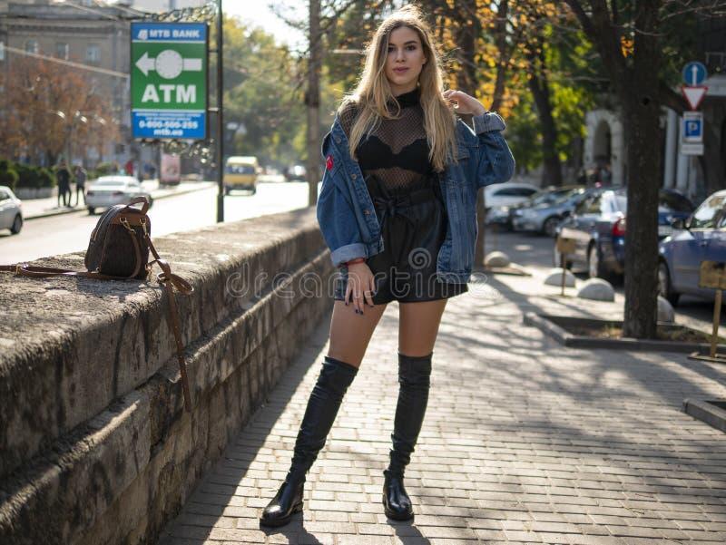 Attraktive Blondine mit dem flüssigen Haar in den Lederstiefeln, die auf der Straße im vollen Wachstum stehen lizenzfreies stockfoto