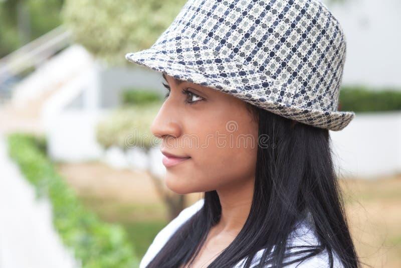Attraktive brasilianische Frau mit dem Hut, der seitlich schaut stockbild