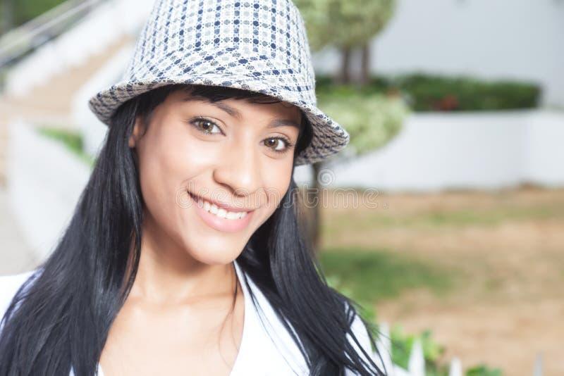 Attraktive brasilianische Frau mit dem Hut, der seitlich schaut lizenzfreie stockbilder
