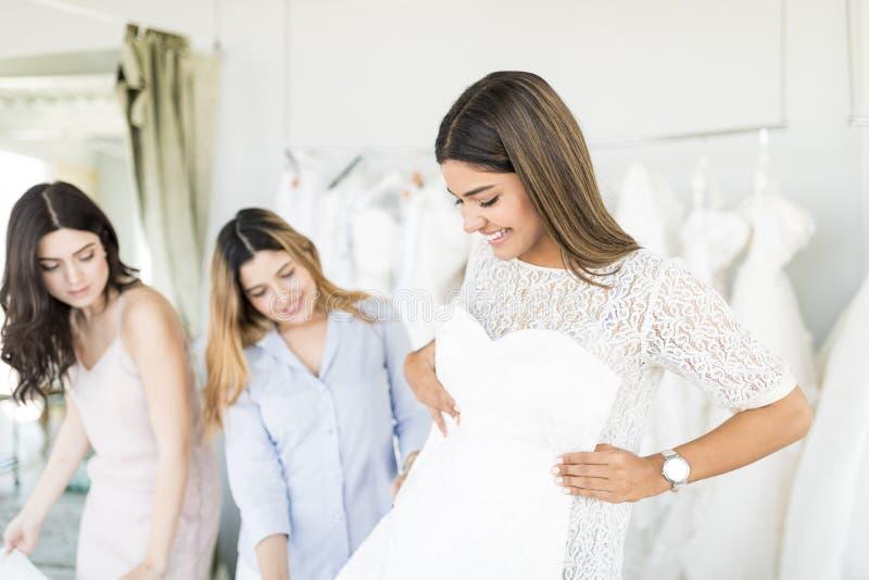 Attraktive Braut, die ein Heirats-Kleid im Speicher wählt stockfotos