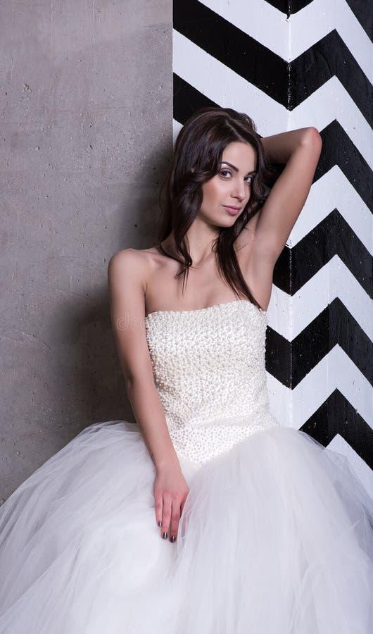 Attraktive Braut im weißen Hochzeitskleid, das an der Wand mit Schwarzweiss-Streifen aufwirft stockbild