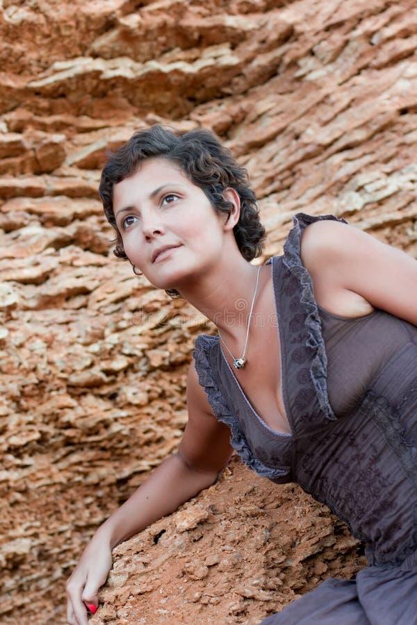 Attraktive Brunetfrau unter Felsen lizenzfreie stockbilder