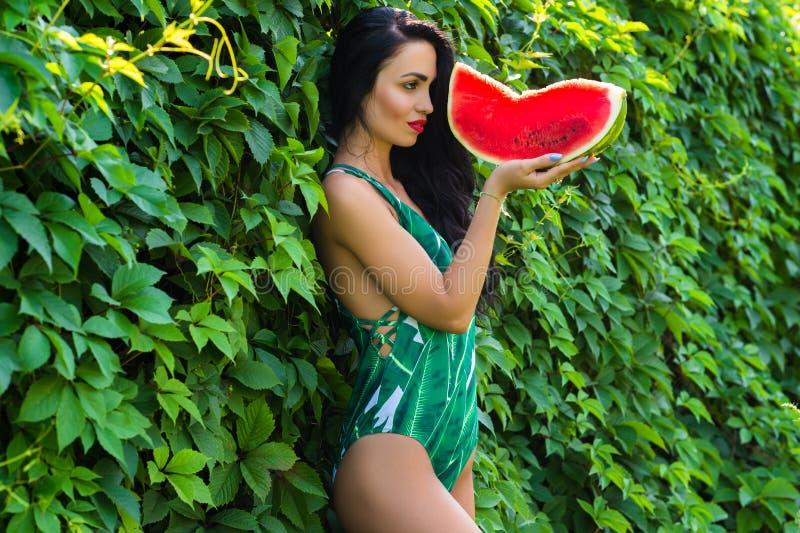 Attraktive brunette Frau im grünen Badeanzug mit Wassermelone in der Hand stockbilder