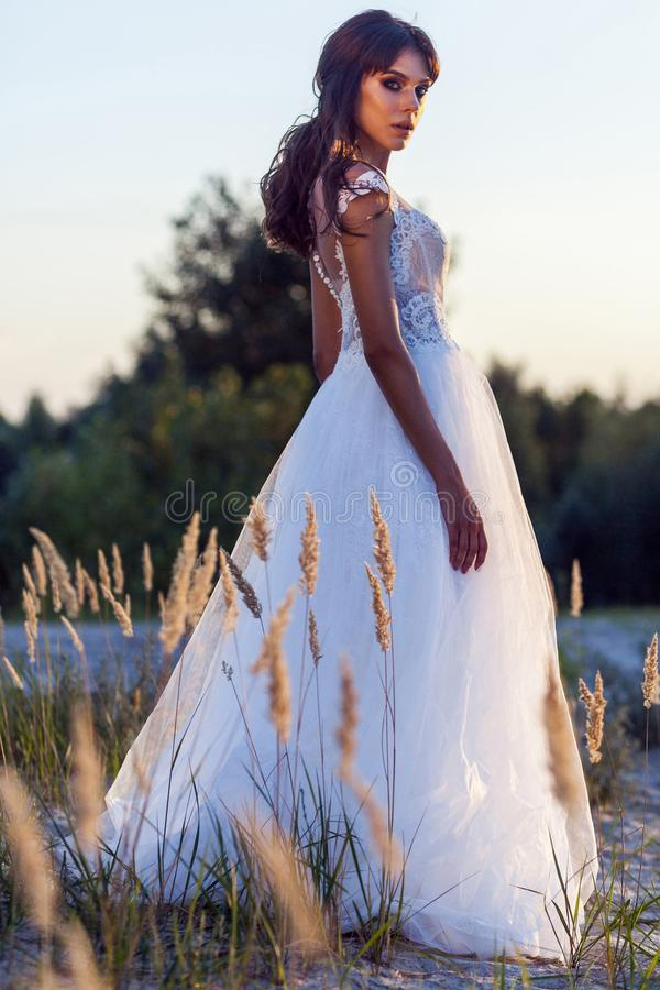 Attraktive brunette Frau mit tragendem weißem Heiratskleid des Makes-up und der Frisur bei der Aufstellung in Lichtung Seitenansi lizenzfreie stockfotografie