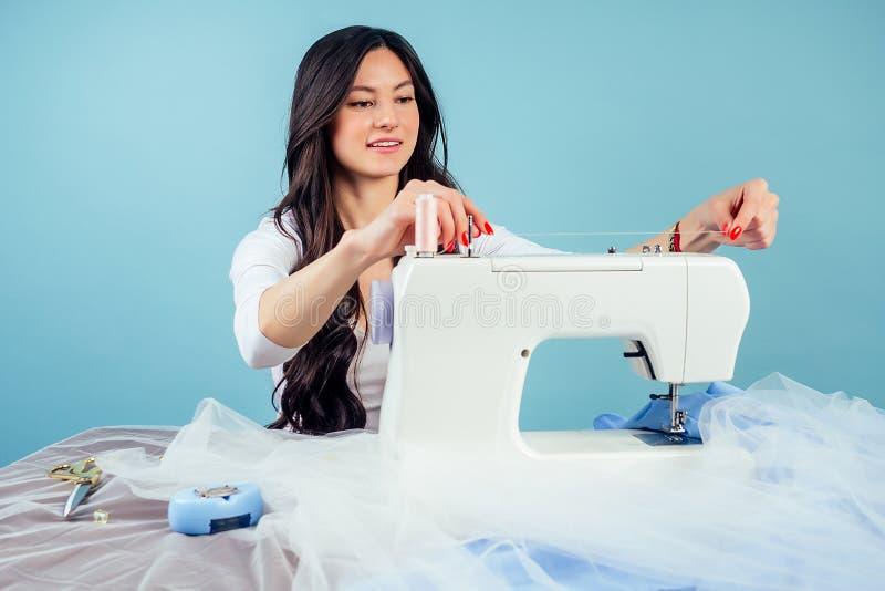Attraktive Brunette-Frau Schneiderin Schneider-Schneider-Schneider-Faden die Nadel auf der Nähmaschine auf einem blauen Hintergru lizenzfreies stockbild