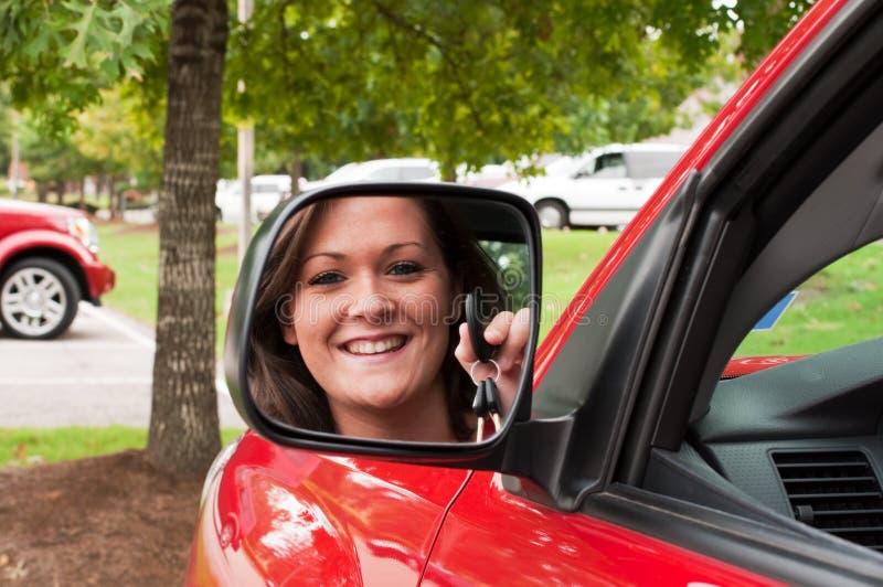 Attraktive Brunette-Holding-Tasten im Fahrzeug-Spiegel stockbild