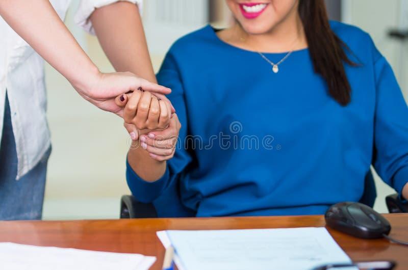 Attraktive Brunettebürofrau, welche die blaue Strickjacke sitzt durch den Schreibtisch empfängt Handmassage, Entspannungskonzept  stockfoto