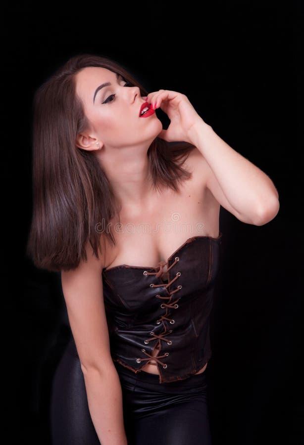 Attraktive Brunettefrau auf Studiodunkelheitshintergrund stockbilder