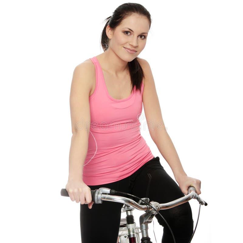 Attraktive Brunettefrau mit Fahrrad stockbild