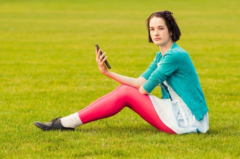 Attraktive Brunettefrauenholding und die Anwendung der digitalen Tablette übertreffen stockbild