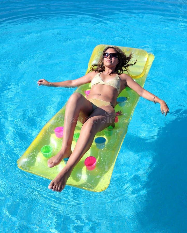 Attraktive, dünne junge Dame, die auf aufblasbarem sunbed auf swimmi liegt stockbilder