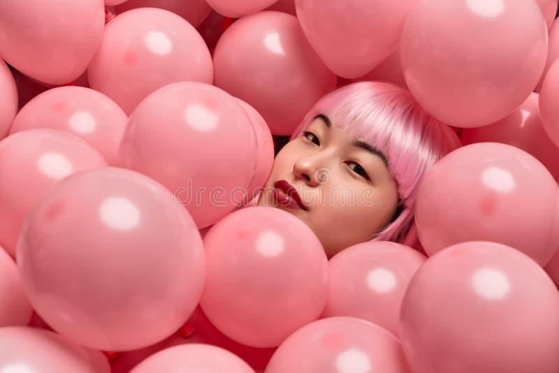 Attraktive Dame in der rosa Perücke, die unter Ballonen liegt stockbild