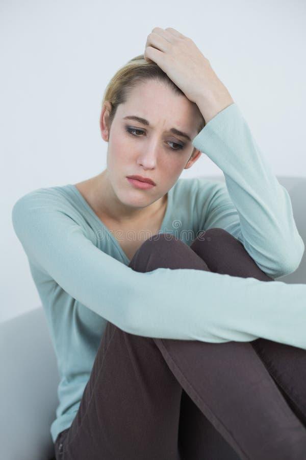 Attraktive durchdachte Frau, die auf Couch sitzt lizenzfreies stockfoto
