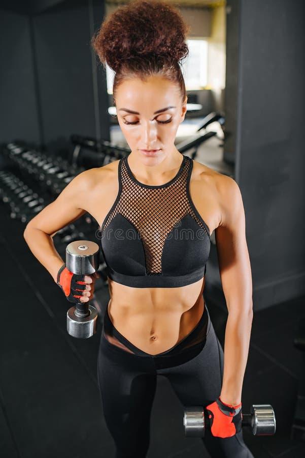 Attraktive Eignungsfrau in der schwarzen Sportkleidungsspitze und Leggins mit dem perfekten Körper, der in der Turnhalle aufwirft stockbilder