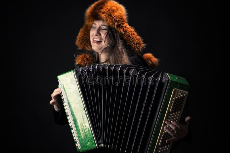 Attraktive emotionale Frau im Pelzhut, der das Akkordeon spielt stockfoto