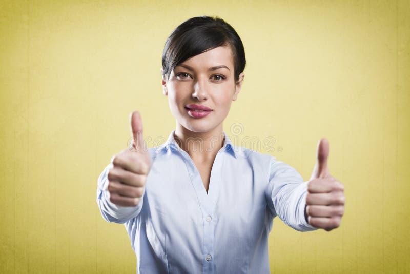Attraktive erfolgreiche Geschäftsfrau, die Daumen aufgibt stockfoto