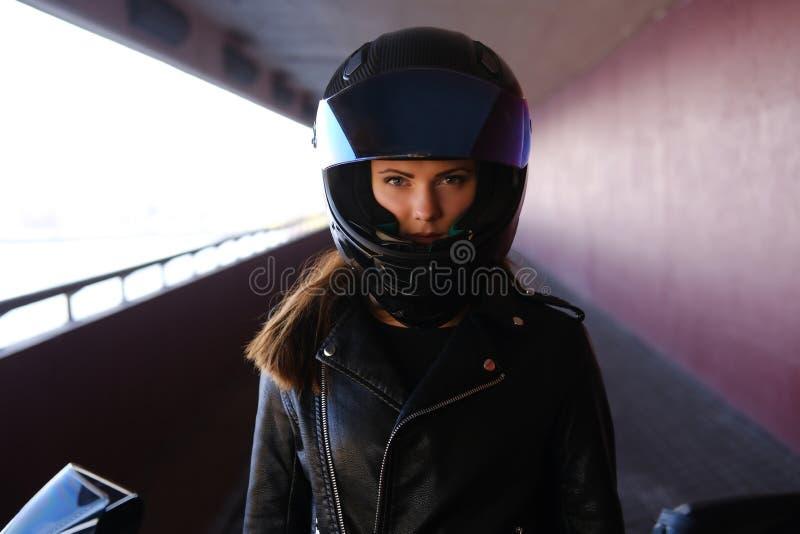 Attraktive ernste Frau steht nahe bei ihrem motobike lizenzfreie stockbilder