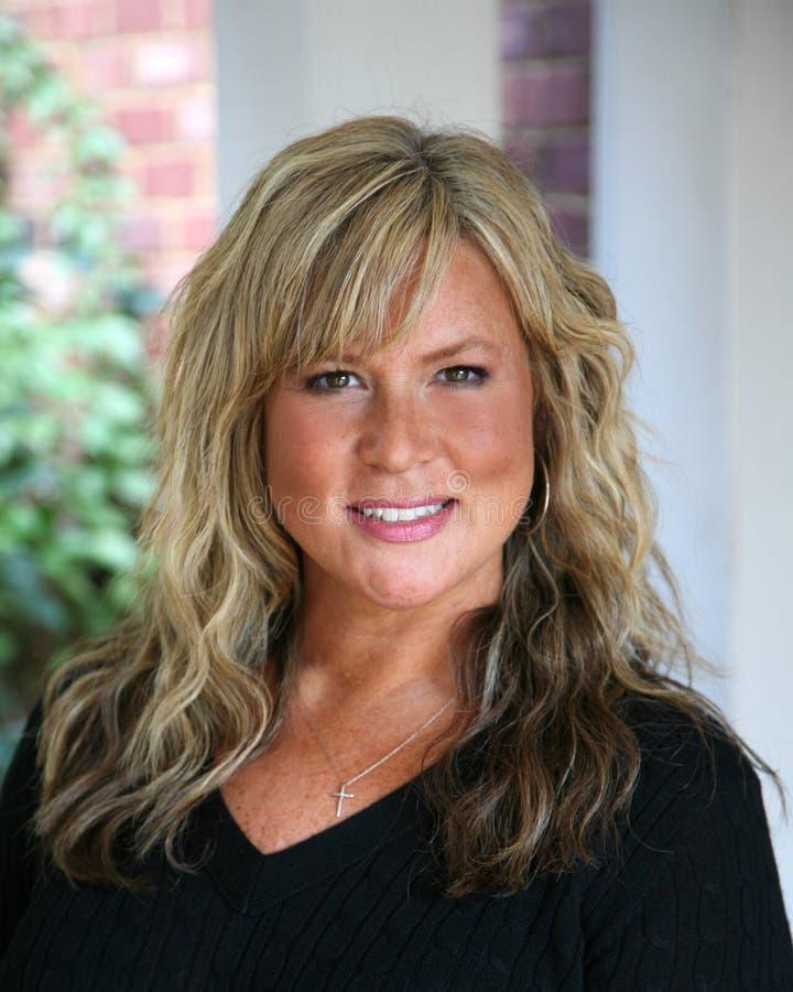 Attraktive, fällige blonde behaarte Geschäftsfrau stockfoto