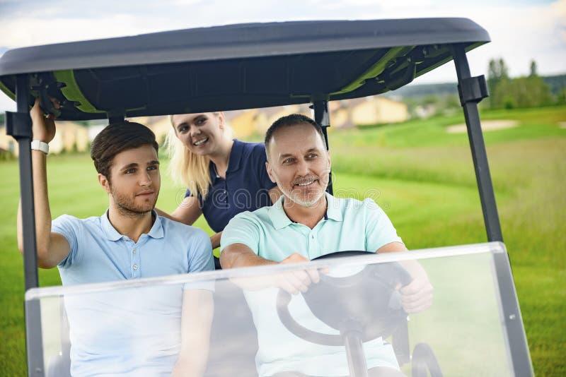 Attraktive Familie in ihrem Golfmobil stockbild