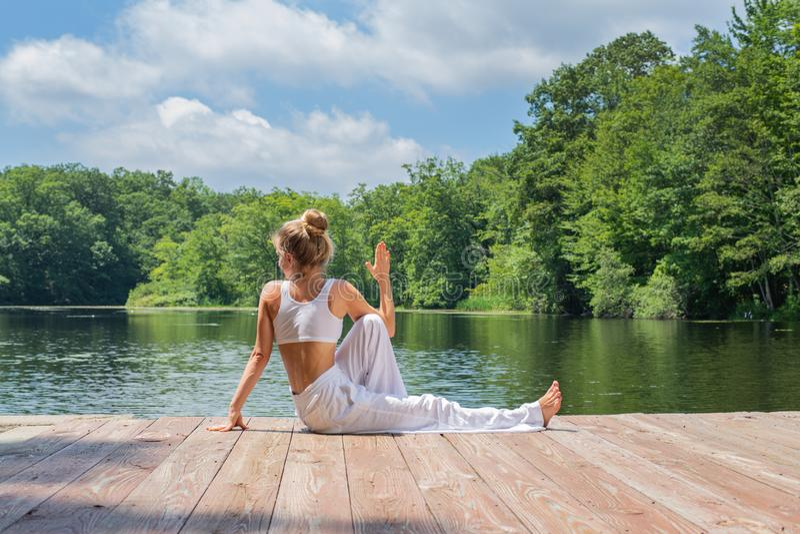 Attraktive Frau übt das Yoga, das in Haltung Ardha Matsyendrasana nahe See am Morgen sitzt stockbilder
