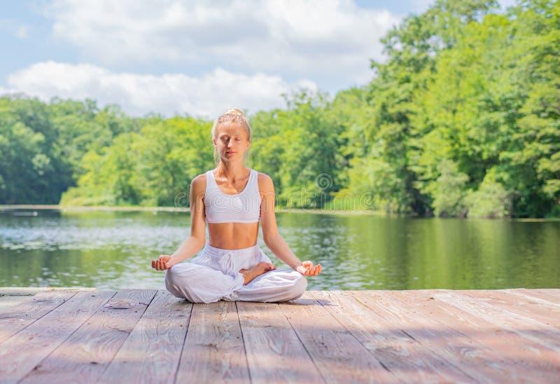 Attraktive Frau übt das Yoga und Meditation und sitzt in der Lotoshaltung nahe See am Morgen lizenzfreies stockfoto