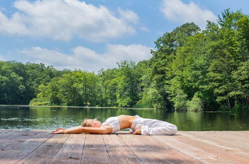 Attraktive Frau übt Yoga und Meditation in Haltung Supta Virasana nahe See am Morgen stockbilder