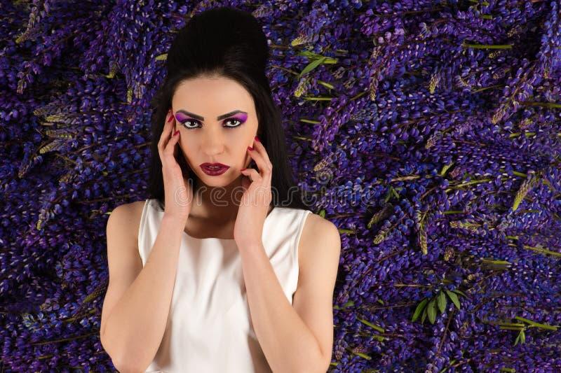 Attraktive Frau auf der Hintergrundwand von Blumen Lupine lizenzfreies stockfoto