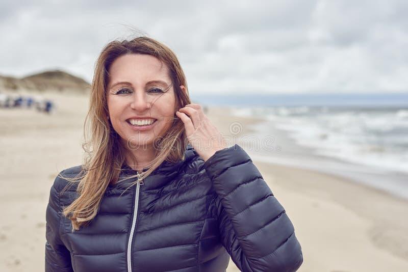 Attraktive Frau auf einem windswept Strand an einem bewölkten Tag lizenzfreies stockfoto