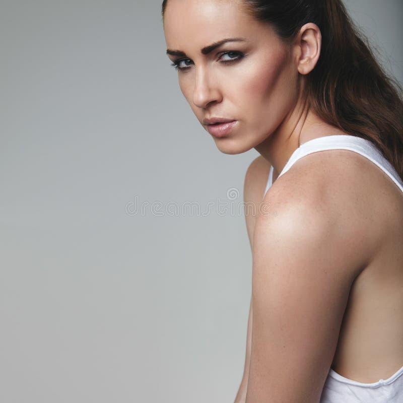 Attraktive Frau auf grauem Hintergrund stockfoto