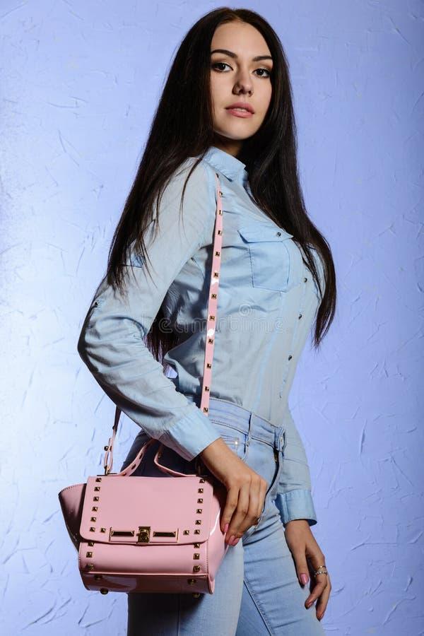 Attraktive Frau in den Jeans mit einer rosa Tasche stockfoto
