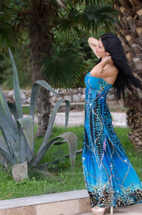 Attraktive Frau der Mode mit blauem langem Kleid lizenzfreie stockfotografie