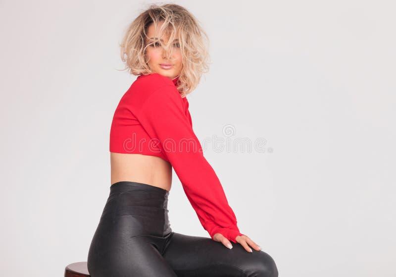Attraktive Frau in der roten Spitze mit blondem unordentlichem Haarsitzen stockfotografie
