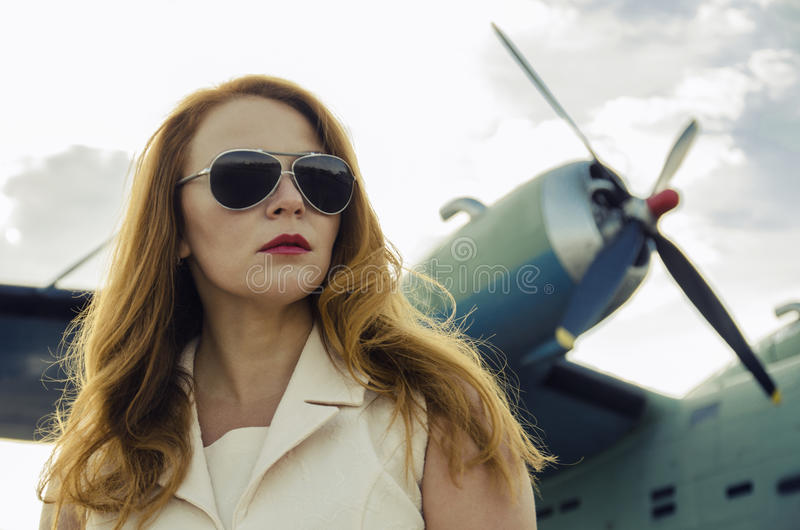 Attraktive Frau in der Sonnenbrille außerhalb der nahen Militärfläche lizenzfreie stockfotos