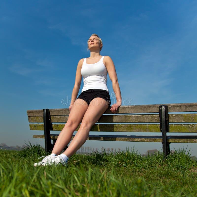 Attraktive Frau in der Sportabnutzung, die einen Bruch nimmt lizenzfreie stockfotos