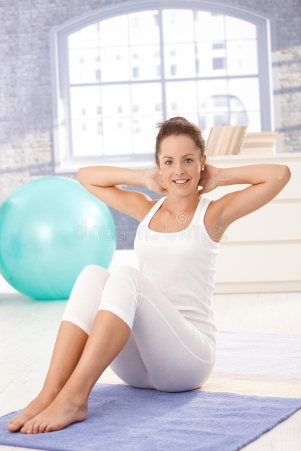 Attraktive Frau, die Übungen auf Fußboden tut stockbilder