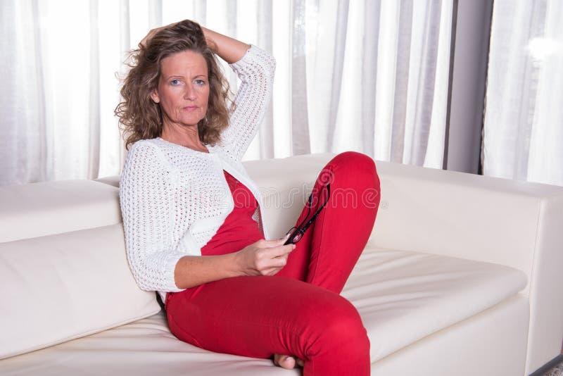 Attraktive Frau, die auf Couch und dem Denken sitzt stockbilder