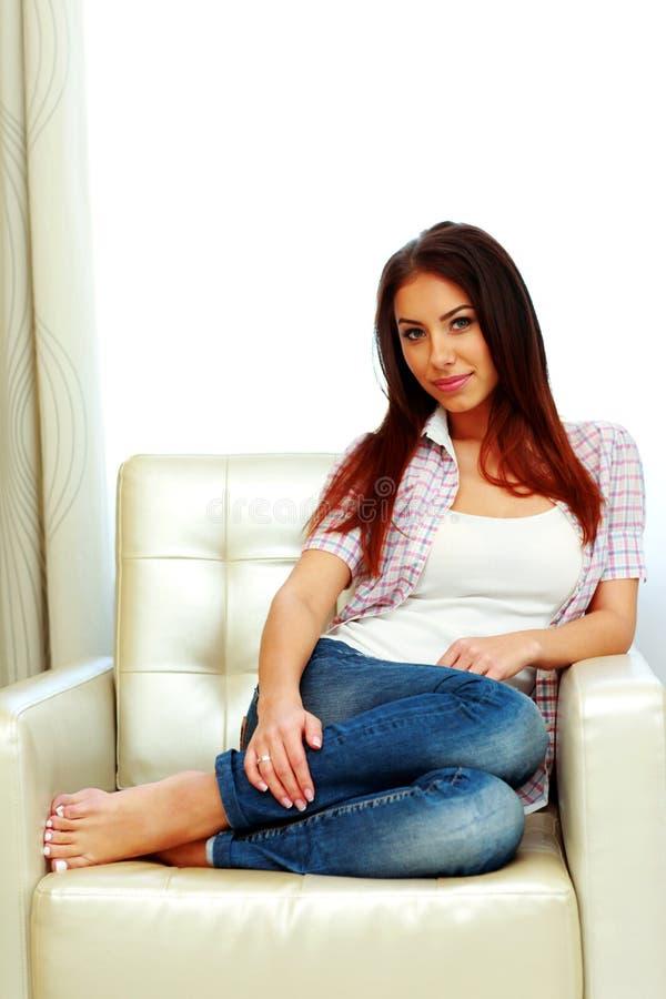 Attraktive Frau, die auf dem Sofa sitzt lizenzfreie stockfotos