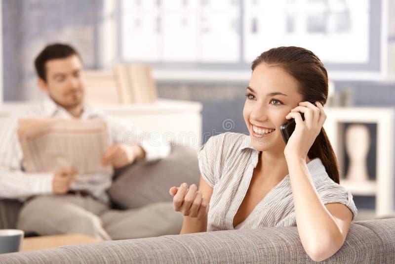 Attraktive Frau, die auf dem Telefonlächeln spricht lizenzfreies stockbild