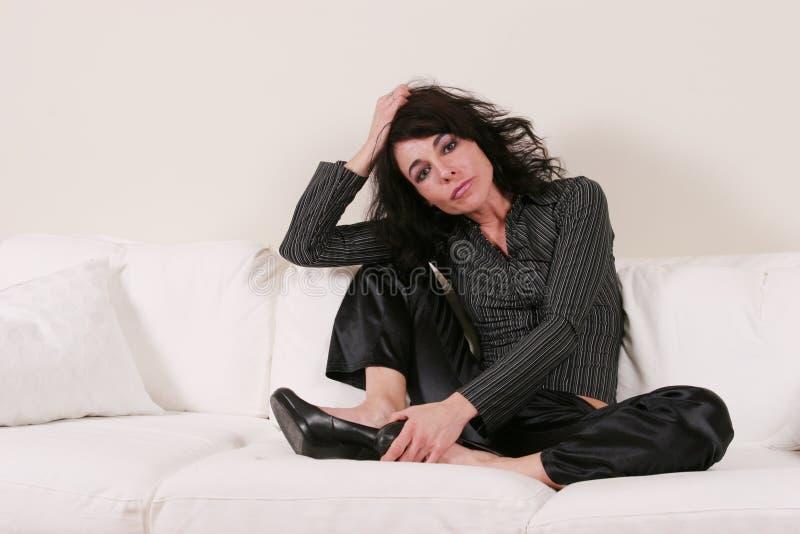 Attraktive Frau, die auf einer Couch sitzt stockfoto